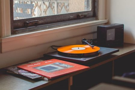 An orange record playing on a classic turntable.