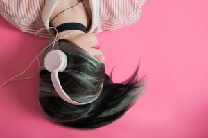 A girl listens to music on her headphones.
