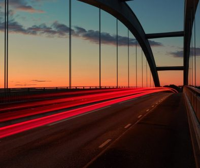 Trailing brake lights over a bridge at sunset.