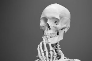 A skeleton sits alone thinking.