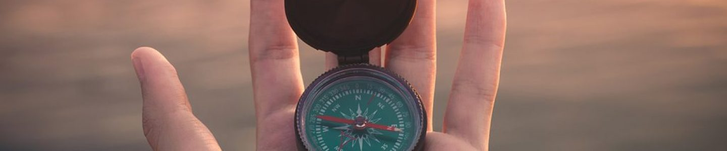 Close-up of mans hand holding a compass.