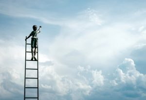 Statue of a a boy on a ladder reaching out to a blue sky full of clouds.