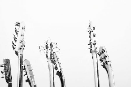 A group of guitars stand against a white wall.