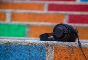 A pair of headphones sits on a colorful wall.