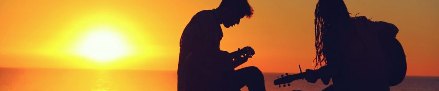 Playing guitars on the beach at sunset.